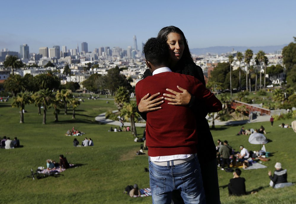 Julie Rajagopal hugs her 16-year-old foster child from Eritrea after posing for photos at Dolores Park in San Francisco.