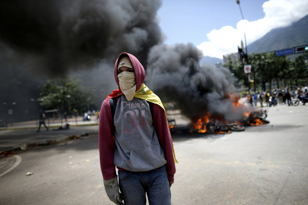 A demonstrator walks near a pile of burning motorcycles during clashes between police and anti-government protesters in Caracas, Venezuela, on Sunday. After an explosion injured several officers, police were seen throwing privately owned motorcycles into the fire.