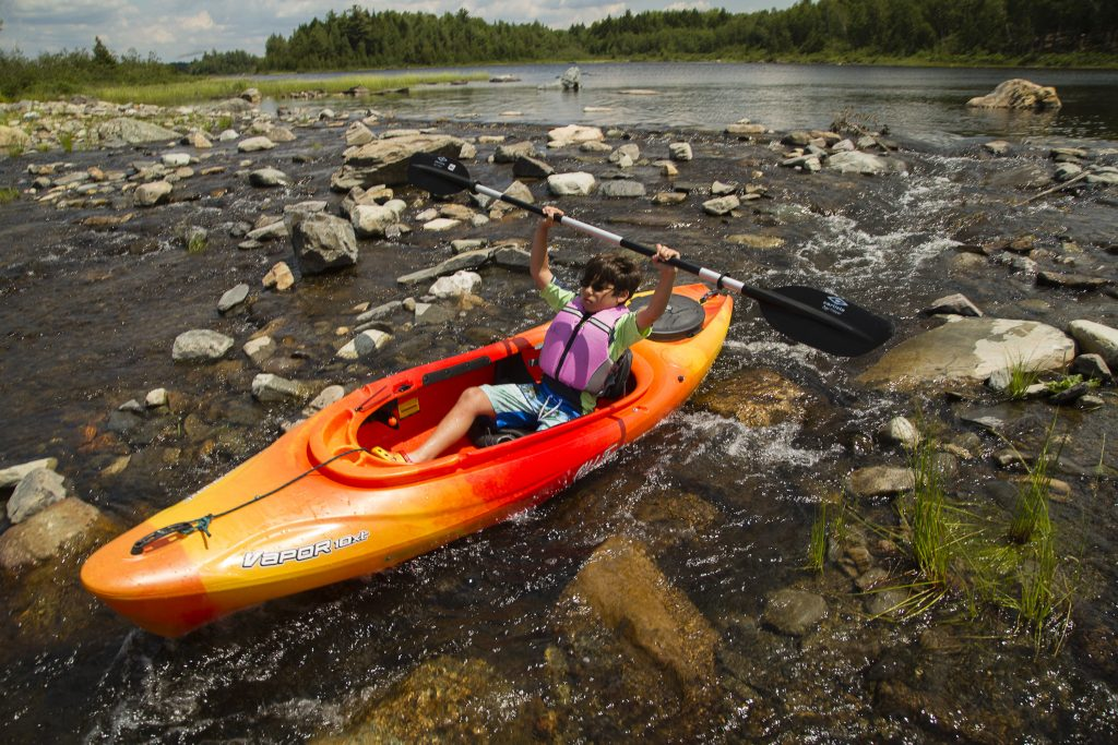 Tyler Flory, 10 of Amherst, Mass., rides a kayak through a mini rapid at the out flow of Third Roach Pond.