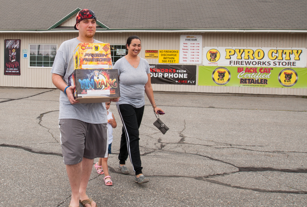 Stocking up on fireworks for July Fourth are Leland, left, and April Kelley, of Dedham, Mass., with their 3-year-old daughter Lea. They are visiting family in Maine and stopped at Pyro City Fireworks in Manchester on Saturday.