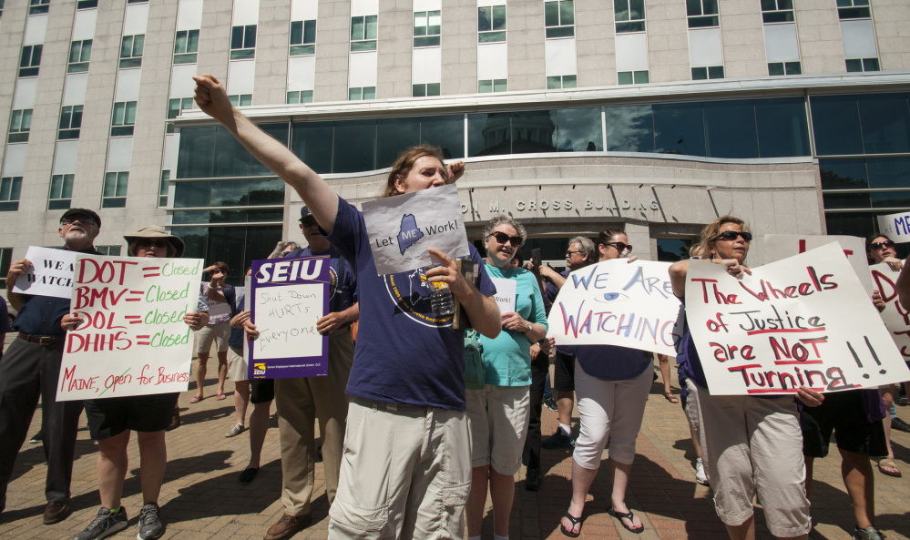 State employee union members protest the state shutdown by rallying Monday in front of the Burton Cross State Office Building in Augusta.