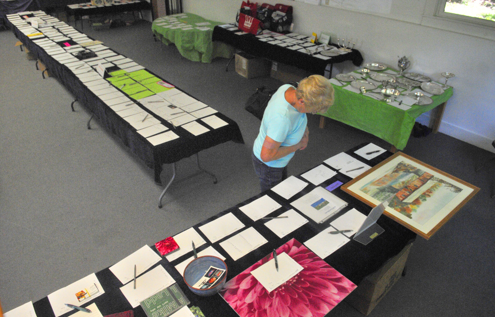 A parishioner takes a peek at items up for silent auction on July 6, 2016, at the Wayne Community Church in Wayne. The auction is a fundraiser for the church and will be held this year from Thursday through Saturday.