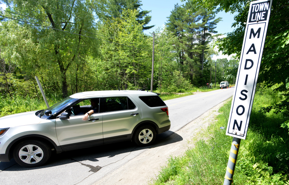 A Maine State Police trooper turns vehicles around Wednesday on Russell Road at the town line separating Skowhegan and Madison as investigators work at the scene of four fatal shootings.