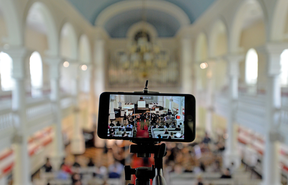 Members of the Atlantic Music Festival perform as a phone records from the balcony Saturday at Lorimer Chapel at Colby College in Waterville.
