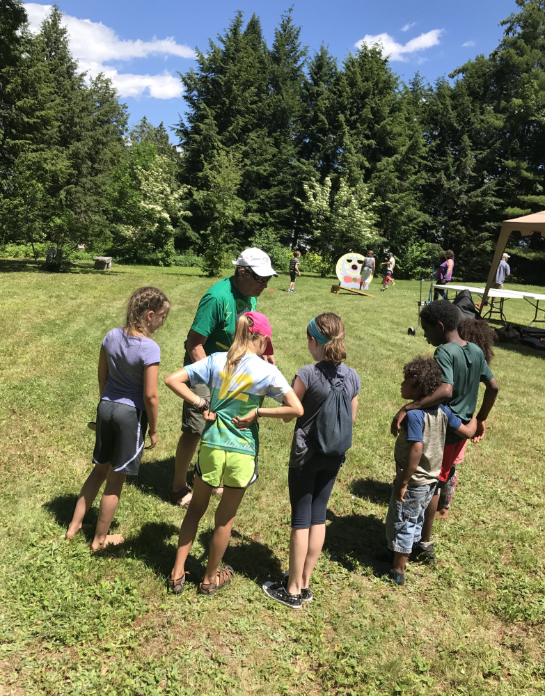 Peter Walsh, center, explains the rules of the upcoming foot race to the children he rounded up to take part at Dresden's SummerFest on Sunday at the Pownalborough Court House.
