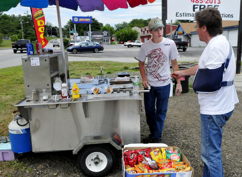 Dana Purington, left, owner of Dana's Dogz food stand, takes money from customer Jeff Greenlaw at his mobile hot dog stand parked off Maine Avenue in Farmingdale on Monday.