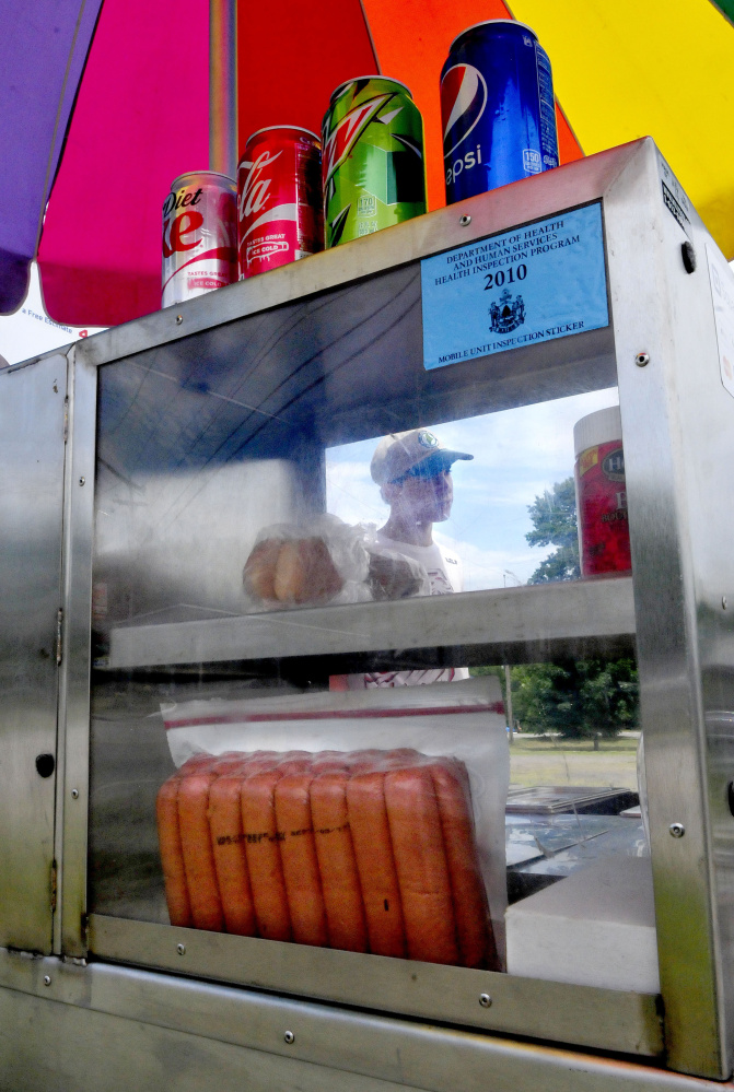 Staff photo by David Leaming Dana Purington, owner of Dana's Dogz food stand, is seen through the steamed windows of his mobile hot dog stand parked off Maine Avenue in Farmingdale on Monday.