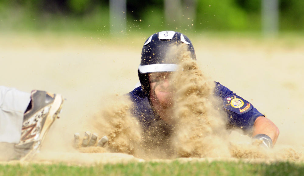Augusta baserunner Dylan Brown slides safely into first base to avoid being picked off during an American Legion Zone 2 game against Gardiner on Tuesday at Hoch Field in Gardiner.