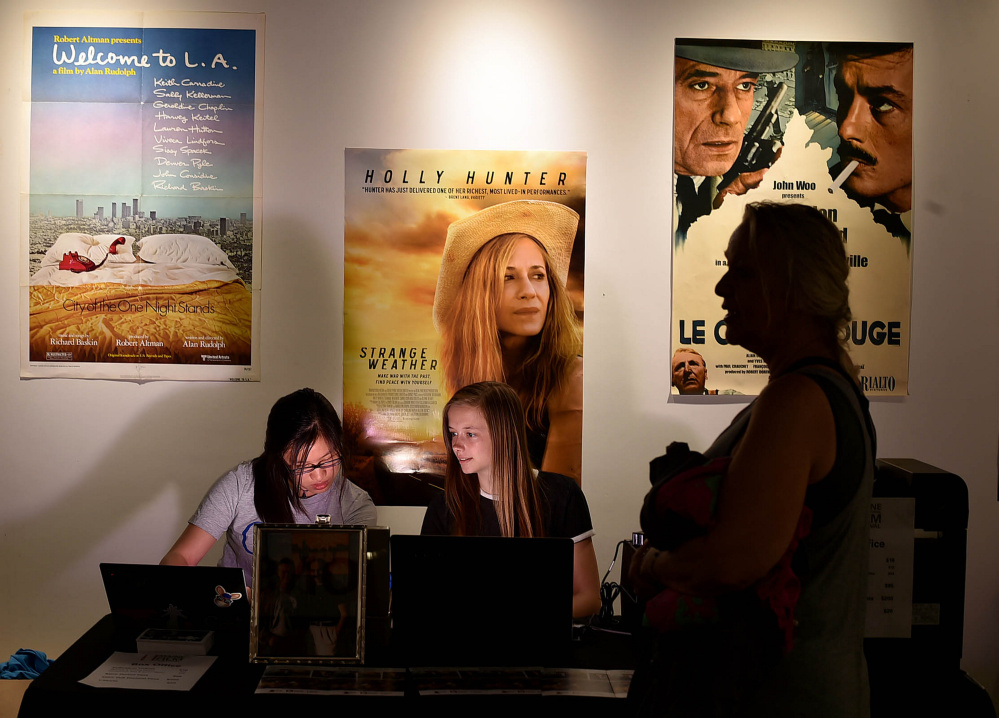 Sunny Dangui, left, and Amanda Schmidt, center, sell a MIFF pass Wednesday to Edda Thiele, right, at Railroad Square Cinemas in Waterville.
