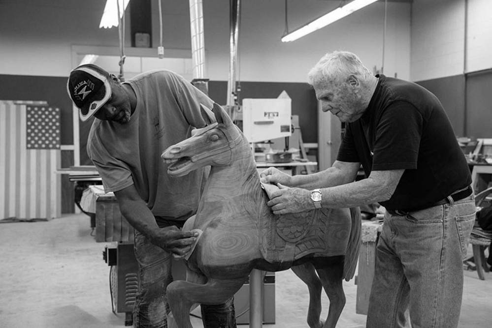 "Ramsy Uter and Tom Moser work on their carving of a small carousel horse that will be making its debut at the Maine State Museum's upcoming exhibition, ""Thos. Moser: Legacy in Wood,"" on view for six months beginning July 15."