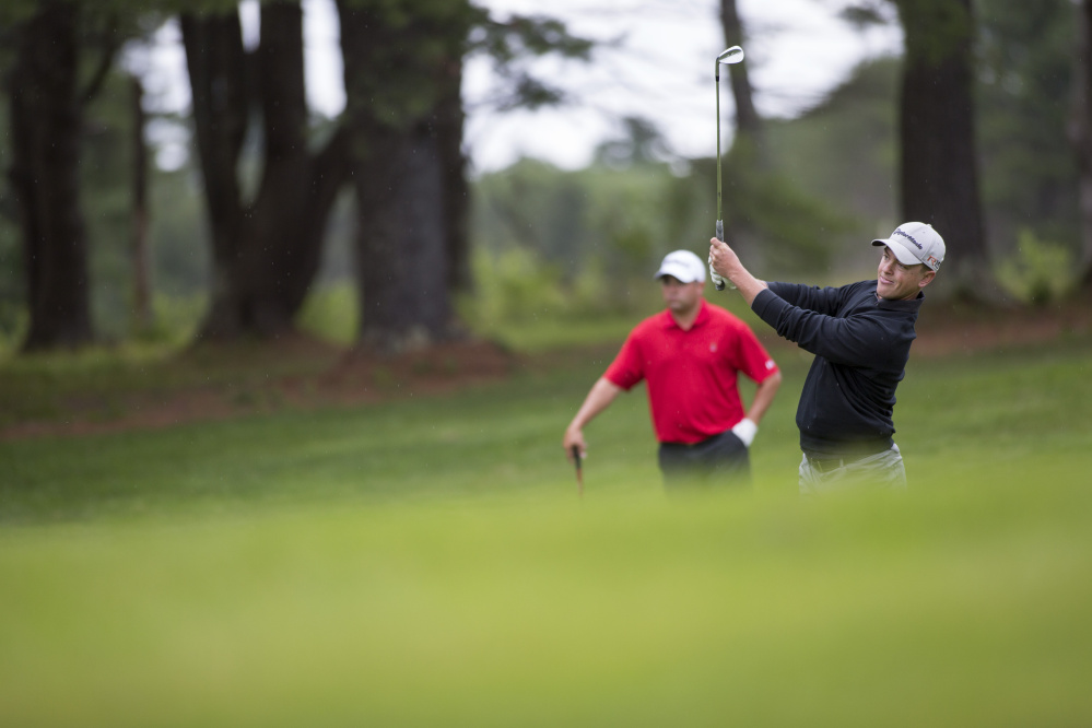 Sam Grindle, left, looks on as Jack Wyman hits a shot during the final round of the Maine Amateur golf tournament Thursday at the Brunswick Country Club.
