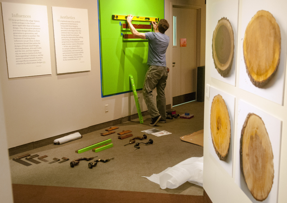"Maine State Museum exhibits preparator Ryan Walker builds shelves for levels and other tools in the entryway to the ""Thos. Moser: Legacy in Wood"" exhibition under construction Tuesday at the museum in Augusta. The exhibit opens Saturday and runs through Jan. 13, 2018."