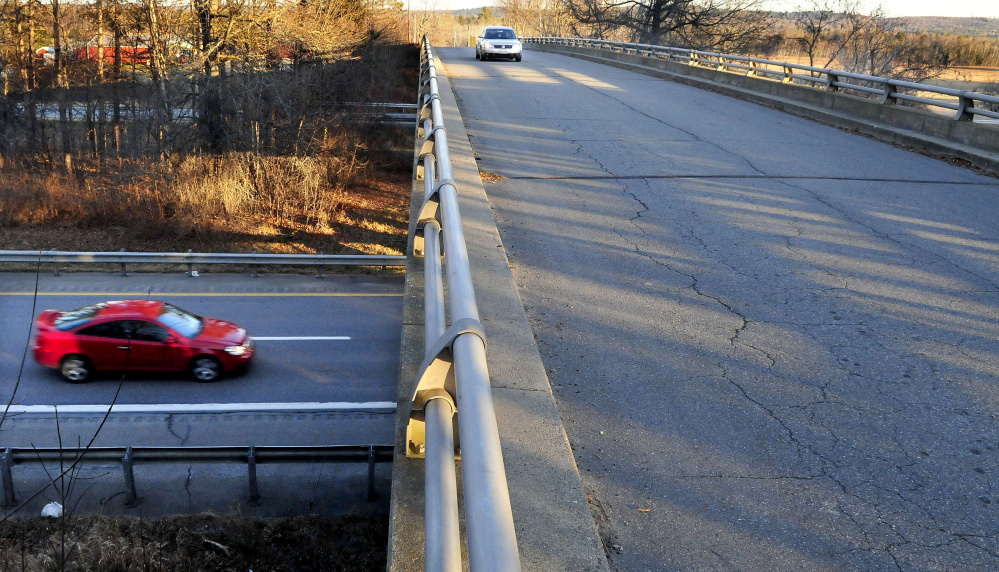 A vehicle travels west Nov. 30, 2015, on Trafton Road in Waterville as another passes under the overpass crossing Interstate 95. A new interchange that opened at the site Friday provides a connection to the highway and offers the possibility of more business development in the area.