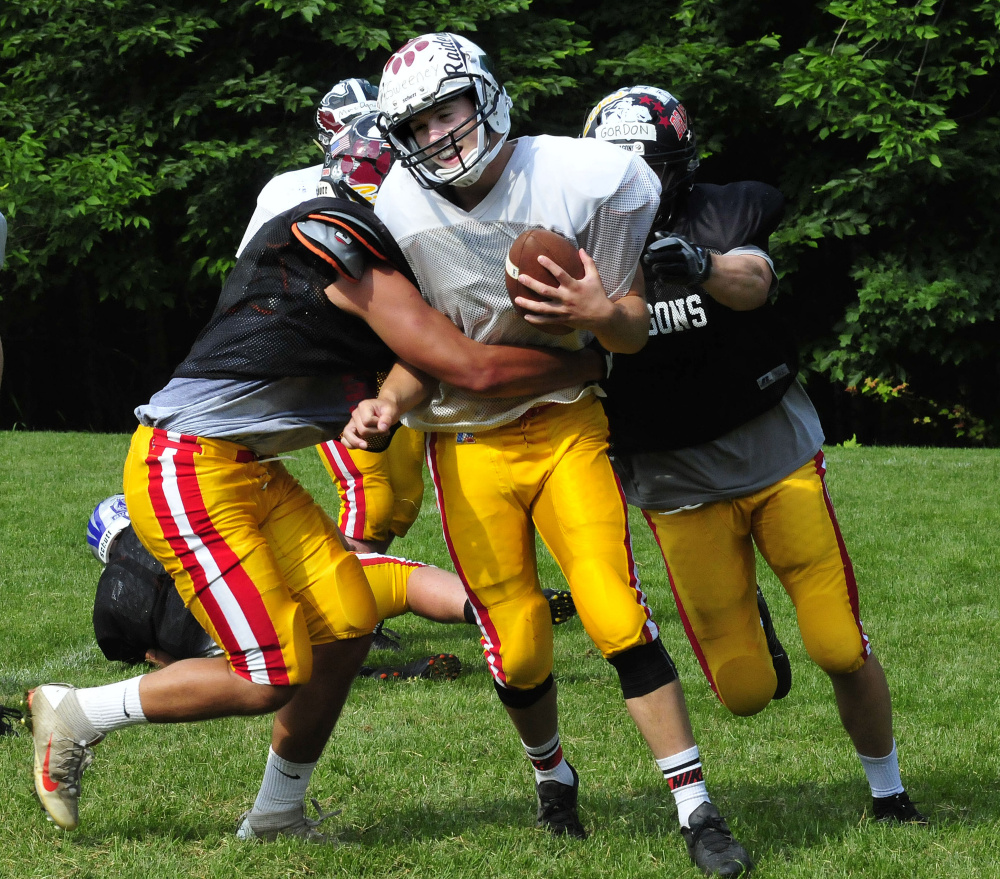 Staff photo by David Leaming East team quarterback Garrett McSweeney gets sacked during practice for the Lobster Bowl on Tuesday at Dover-Foxcroft.