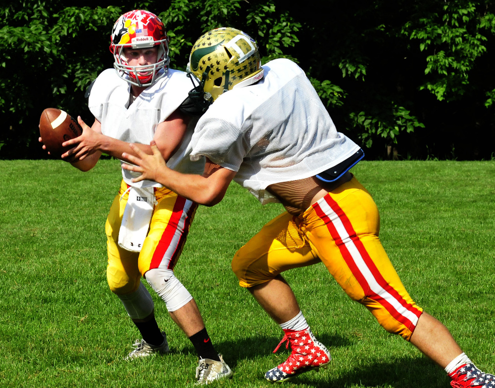 Staff photo by David Leaming East team quarterback Taylor Heath hands off to a teammate during practice for the Lobster Bowl on Tuesday at Dover-Foxcroft.