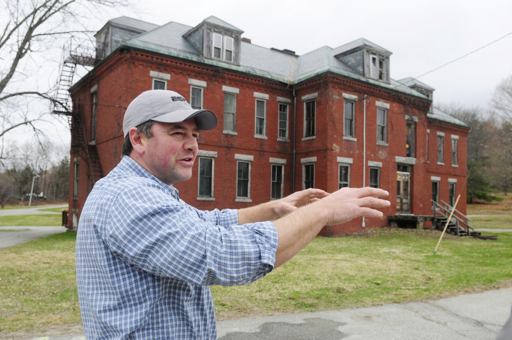 Matt Morrill talks about pulling the ivy off the Erskine Building, in background, while leading an April 20 tour of the Stevens Commons in Hallowell. The City Council on Wednesday will discuss taking ownership of the roads at the complex.