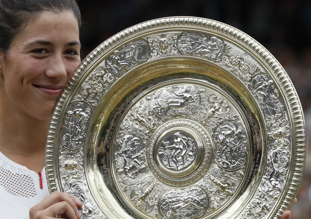 Garbine Muguruza holds the trophy after defeating Venus Williams in the women's Wimbledon final Saturday in London.