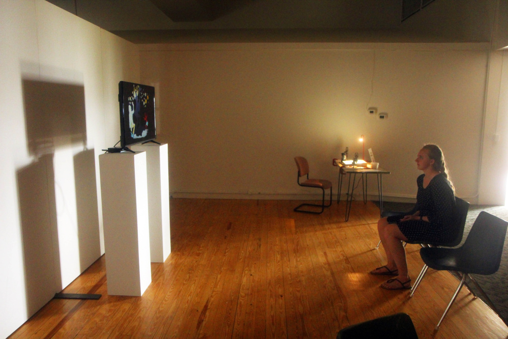Common Street Arts' intern Alyssa Chesney watches a film by Kerry Laitala on Sunday in Waterville at MIFFONEDGE Volume 5, a part of the Maine International Film Festival, which is billed as a way to explore the intersections of art and film.
