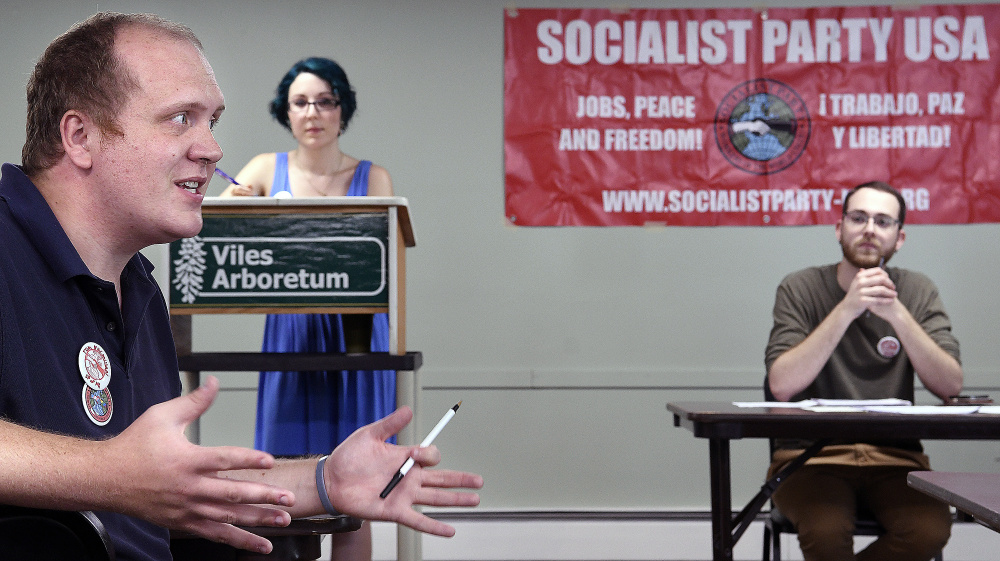 Tom MacMillan, left, Maia Dendinger and Jeremy Claywell on Sunday discuss the platform for the Maine Socialist Party during a meeting in Augusta.