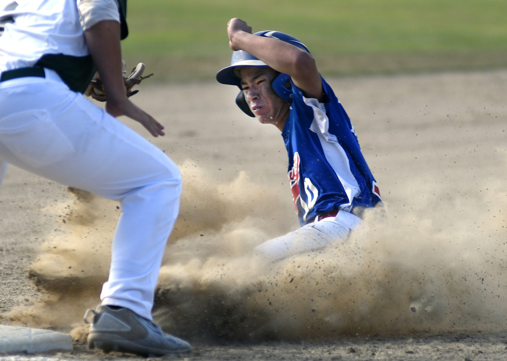 Augusta's Akira Warren slides under the throw to Tri-County's Duncan Jones during the Babe Ruth 14U state championship game against Tri-County on Monday in Augusta.