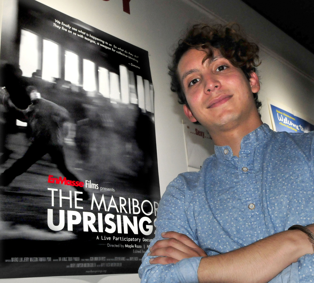 "Milton Guillen, a former Colby student now employed by the college, stands beside a poster of the film ""The Maribor Uprisings"" on Wednesday inside Railroad Square Cinema in Waterville. Guillen co-directed the film, which is being screened at the Maine International Film Festival. Its next showing is scheduled for 9:30 p.m. Saturday at Railroad Square."