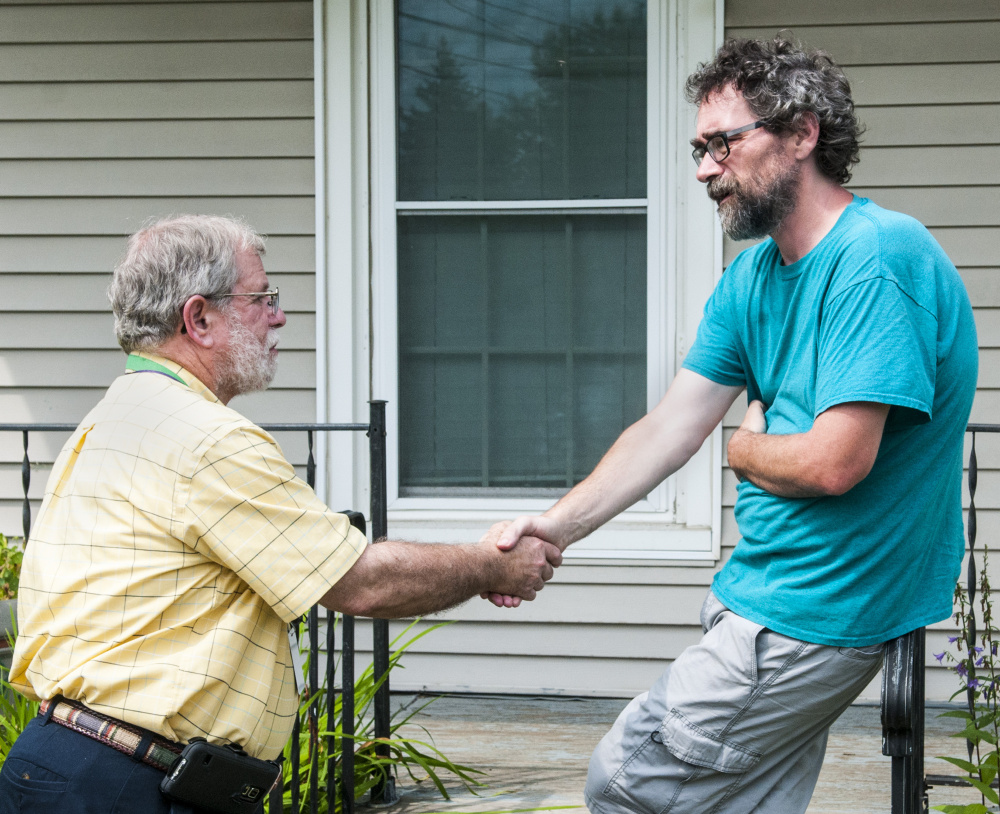 Winthrop School Superintendent Gary Rosenthal chats with parent David Hughes on Thursday at Hughes' home, on the corner of Main and Royal streets in Winthrop. Hughes put up a large sign on his lawn urging fellow residents to reject the school budget Tuesday, saying it is too low.