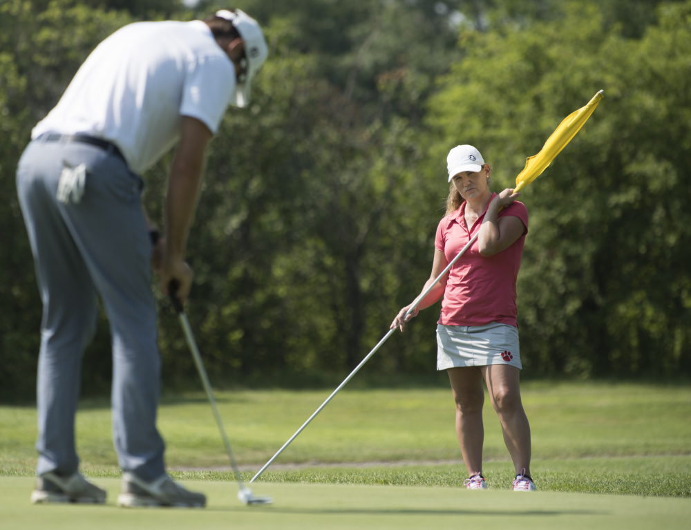 Kristin Ingram, right, of Monticello Arkansas caddies for her friend Matthew Baker, right, of Orlando, Florida on the 3rd hole of Bangor Municipal Golf Course on Friday.