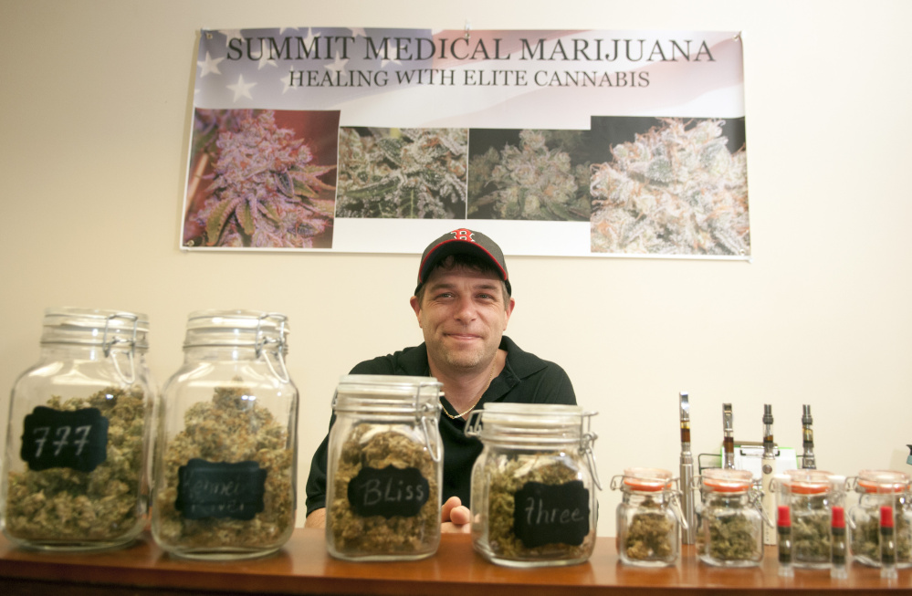 Dennis Meehan with some of the varieties of medical marijuana for sale on July 7 at the new Summit Medical Marijuana storefront on Water Street in Gardiner.