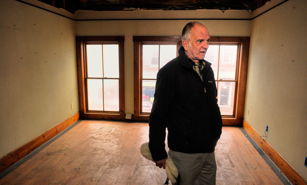 Terry Berry, a Gardiner city councilor who hopes to use federal money to improve the outside of his building on Water Street, looks around inside the building in March during a tour.