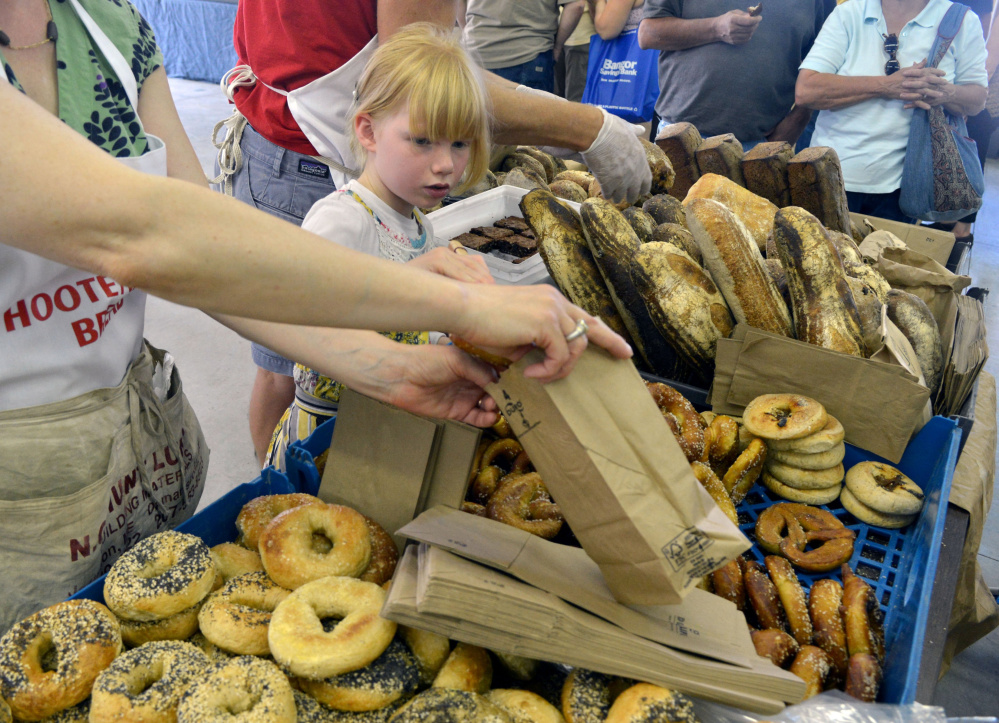 Francis DeGeer (cq), helps her mother, Marcia and father, Derek, fill orders of bread from their bakery table Hootenanny Bread at the Maine Artisan Bread Fair at the Skowhegan Fair Grounds on Saturday, July 30, 2016.