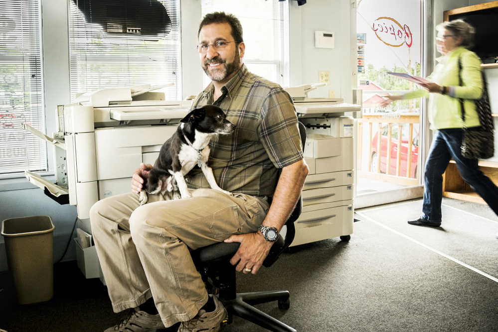 Joey, the dog, sits Monday on the lap of his owner, Larry Violette, at Copies Etc on U,S. Route 202 in Manchester. Joey provides friendly greetings to customers when they visit the family-owned business.