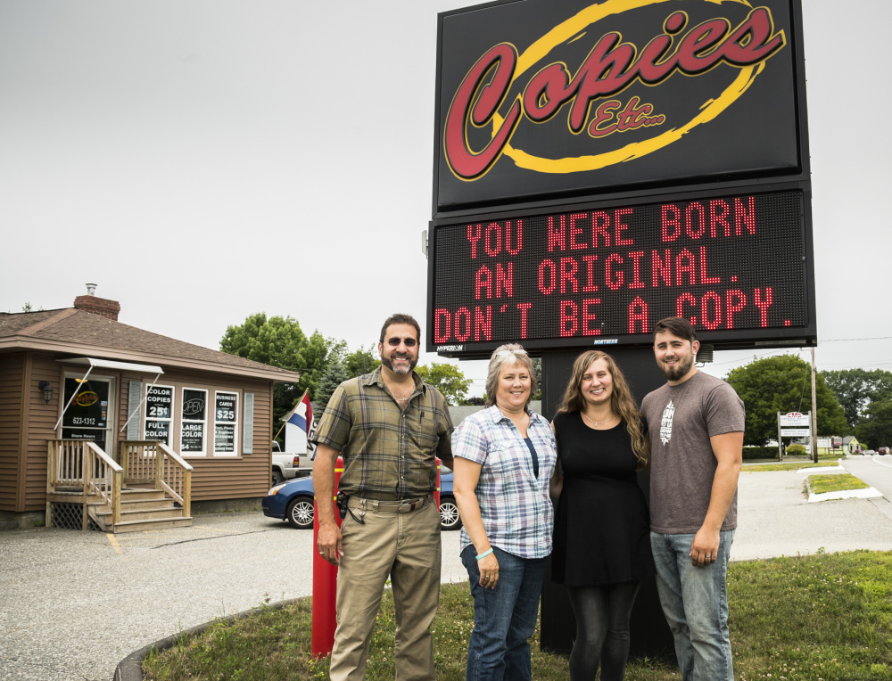 Members of the Violette family stand Monday in front of the Copies Etc electronic sign, known for quotations that entertain and inspire drivers on U.S. Route 202. The family members who work in the shop, from left, are Larry; his wife, Chrystal; daughter Ashley; and son Stephen.