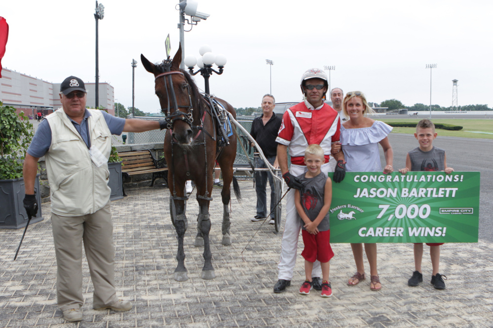 Jason Bartlett, in red an white, stands with his wife and kids after winning his 7,000th career race last Sunday at Yonkers Raceway in Yonkers, New York. Bartlett is a Windsor native and Erskine Academy graduate.