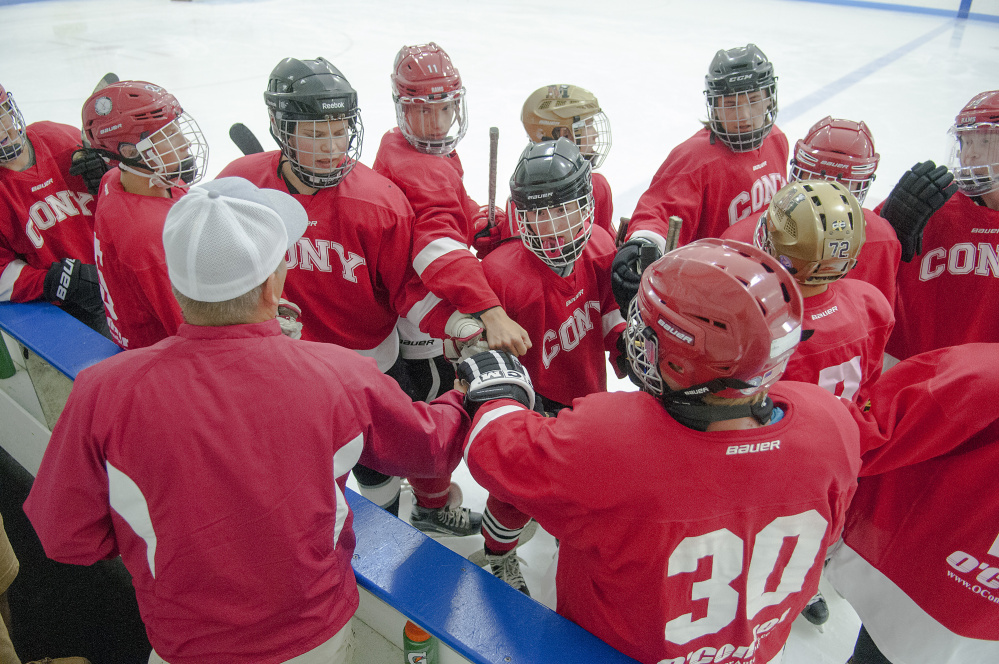 Coach Shawn Johnson, bottom left, rallies his Cony team before a game against Gardiner on Friday at the Camden National Bank Ice Vault in Hallowell.