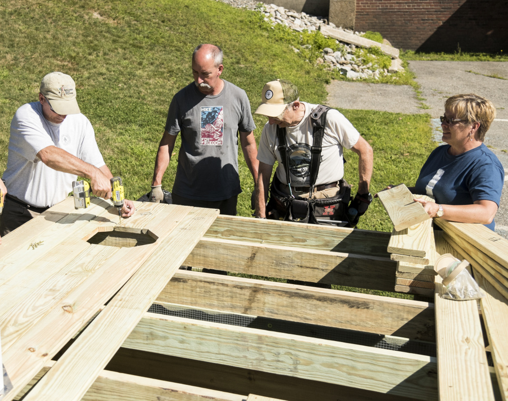 Members of the Maine Appalachian Trail Club build a demonstration privy in advance of the groups' conference at Colby College in Waterville. From left are: Doug Dolan, of Hollis, Richard Gower, of Richmond, Dana Humphrey, of Palmyra, and conference co-chairwoman Sherri Langlais.