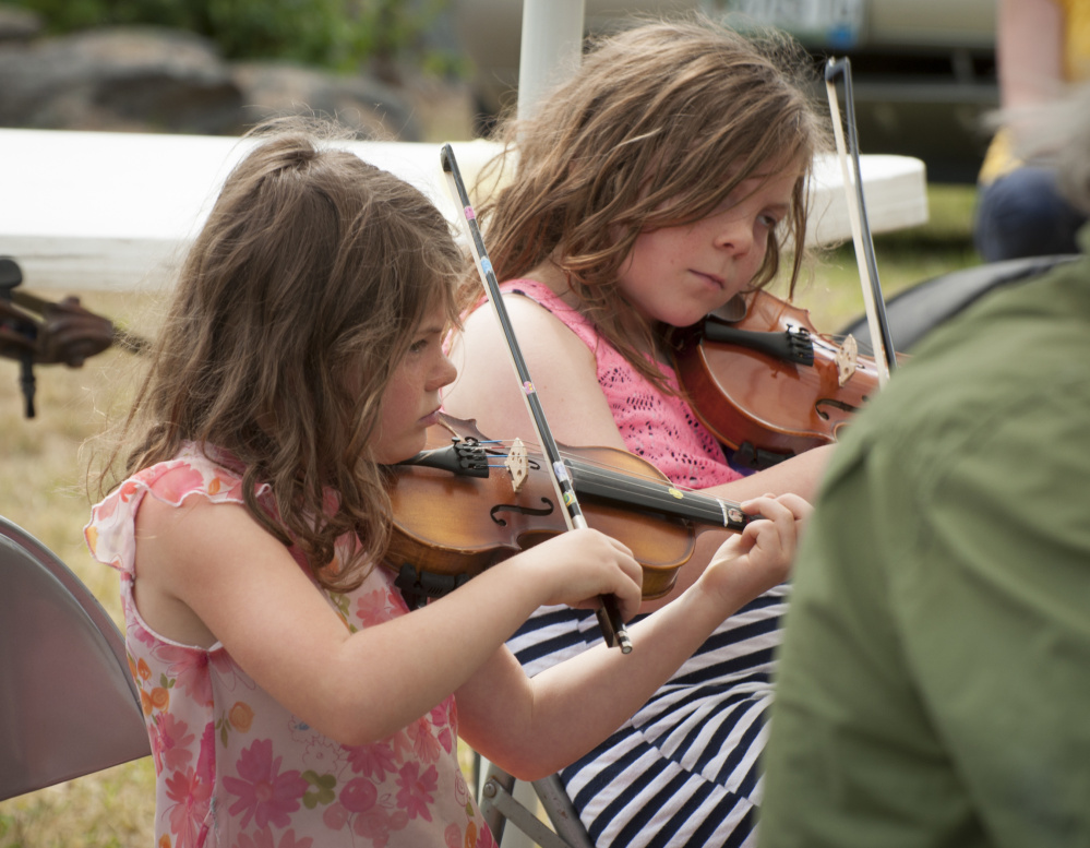 Mary Philbrick, 6, and her sister Allison, 8, of Alna, play their fiddles while jamming with other musicians at the East Benton Fiddle Convention and Contest at Littlefield Farm on Richard's Road.