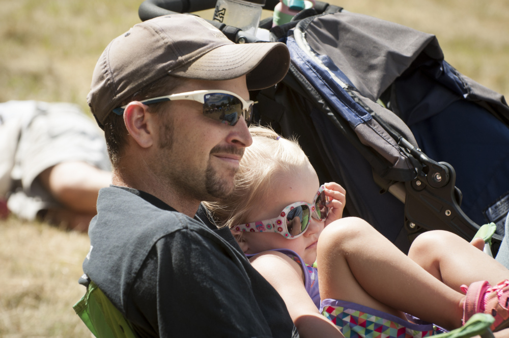 Scott McCormick, of Jackson, holds his daughter, Alice, 3, as they listen to musician being played at the East Benton Fiddle Convention on Sunday in East Benton.