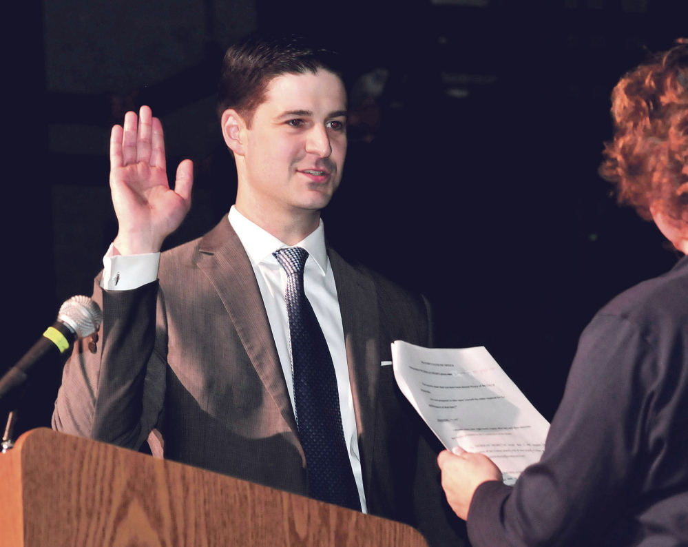 Newly elected Waterville Mayor Nick Isgro takes the oath of office administered by City Clerk Patti Dubois on Jan. 6, 2015. Isgro warned he would veto a budget proposal that included two ed tech IIIs and security cameras for Waterville Senior High School, which the school board voted July 24 to include in their budget.