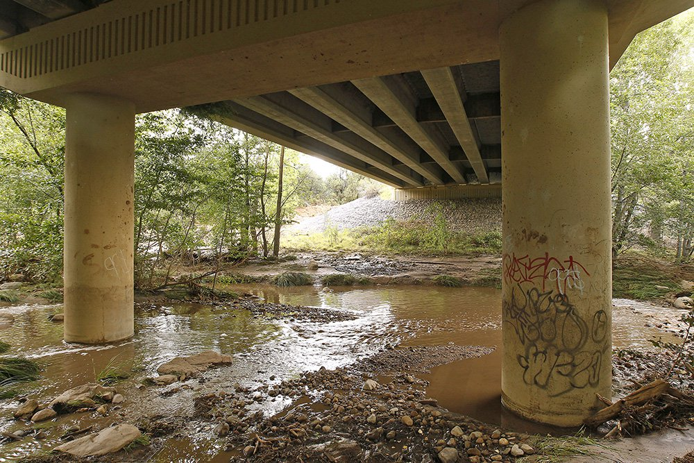 The receding floodwaters of the East Verde River flow under a bridge where at least one victim of a flash flood was found during a search and rescue operation in Payson, Arizona, Sunday.