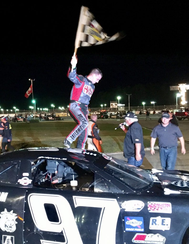 Joey Polewarczyk Jr. of Hudson, New Hampshire, celebrates with the checkered flag after winning the PASS 150 on Saturday night at Beech Ridge Motor Speedway in Scarborough.