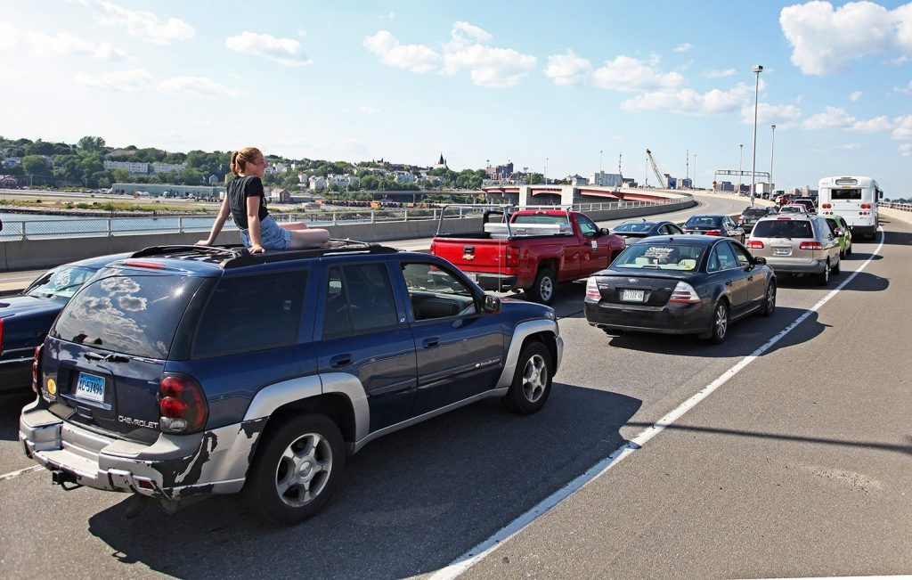 Kris English takes in the view from atop her car as motorists were stranded and rerouted when the arms on the Casco Bay Bridge were stuck.