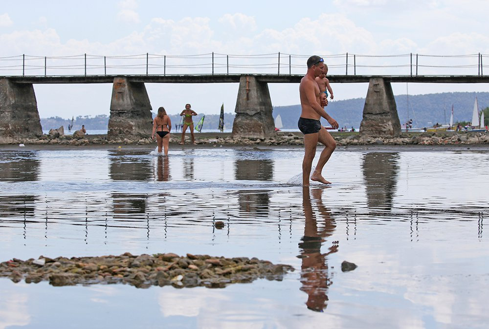 People walk in a shallow area that has emerged in Lake Bracciano north of Rome during the drought. Meteorologists say Italy experienced one of its driest springs in 60 years and that some parts of the country have seen rainfall totals 80 percent below normal.