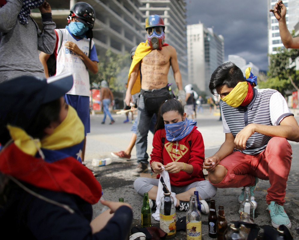 Demonstrators prepare homemade bombs to be used against police during a protest against the installation of a constitutional assembly Friday in Caracas, Venezuela.