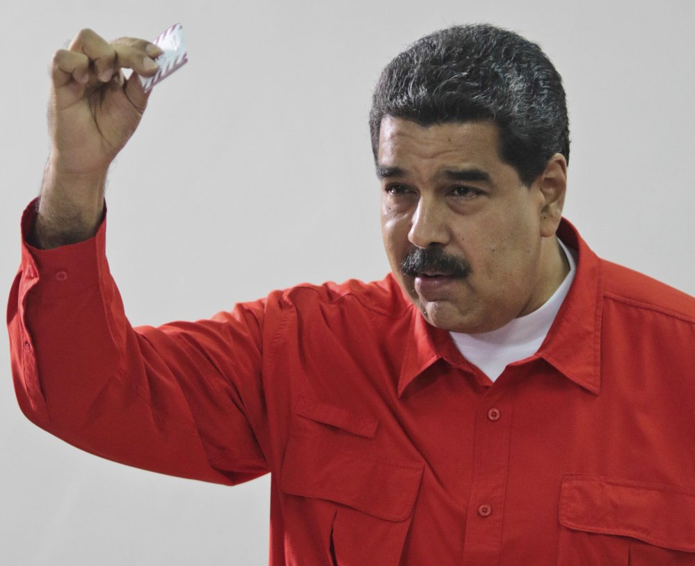 Venezuelan President Nicolas Maduro shows his ballot after casting a vote for a constitutional assembly.