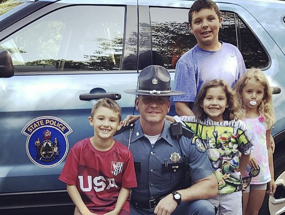 Trooper Nathan Jamo reunites for the first time in six years with four children whom he stood guard over while police searched for their mother's killer. The kids in the front are, left to right, Javanni, Jiselle and Julissa. Ja'kai is in the back.