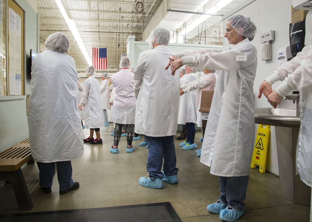 Employees do injury-prevention stretching exercises before their shift at Puritan Medical Products Co. LLC. Puritan and its sister company, with 475 workers, have kept health care premiums low by paying medical claims rather than using a third-party insurer.