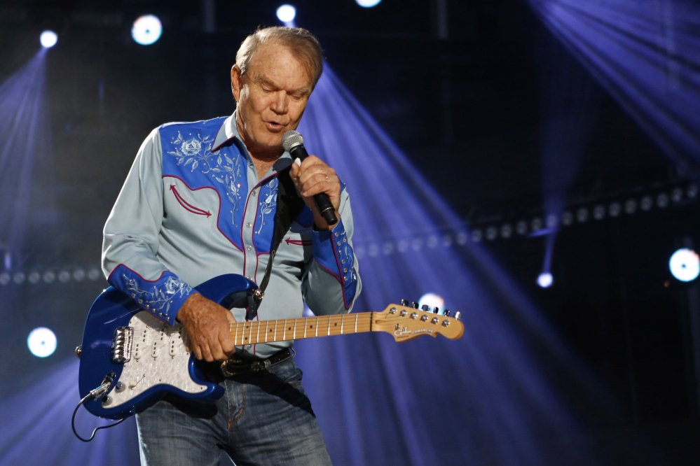 "American country music artist Glen Campbell performs during the Country Music Association Music Festival in Nashville, Tennessee, in 2012. He died in  August at age 81 after a battle with Alzheimer's disease. His hits included ""Rhinestone Cowboy"" and his appeal spanned country, pop, television and movies."