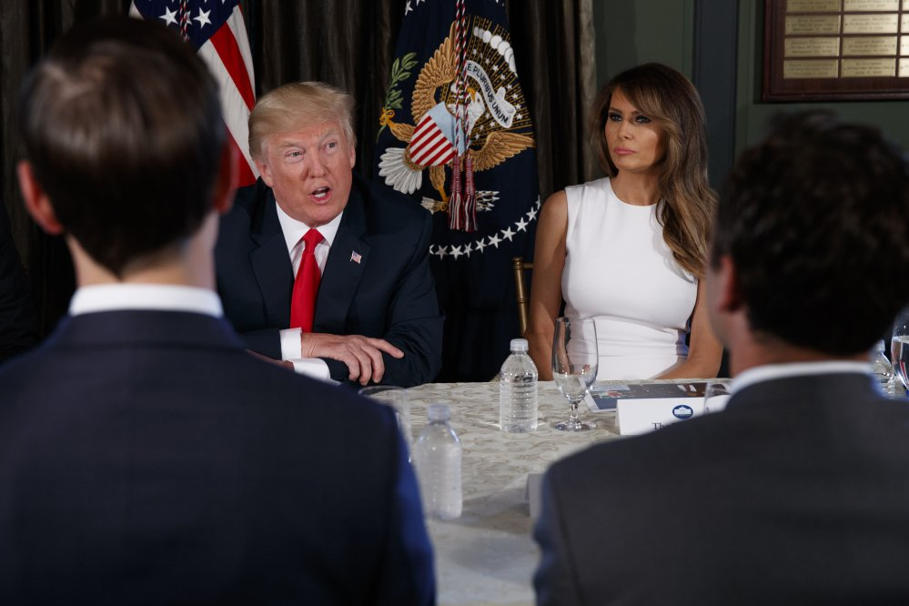 "First lady Melania Trump sits at right as President Trump speaks during a briefing on the opioid crisis on Tuesday at the Trump National Golf Club in Bedminster, N.J., where the president is spending a 17-day ""working vacation."""
