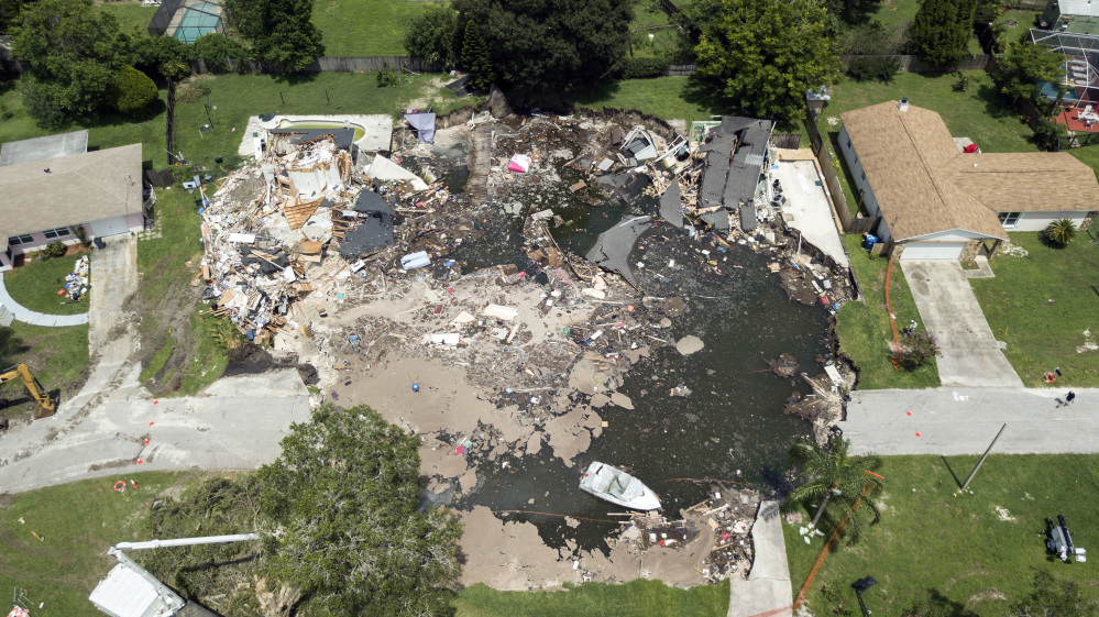 A 260-foot-wide sinkhole, which opened July 14 and swallowed two homes, is shown Friday in Land O' Lakes, Fla. State officials say that more homes could be condemned.