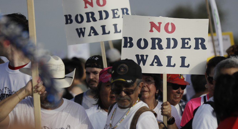 Hundreds of people march along a levee in South Texas toward the Rio Grande to oppose the wall that President Trump wants to build on the river separating Texas and Mexico in Mission, Texas, on Saturday.